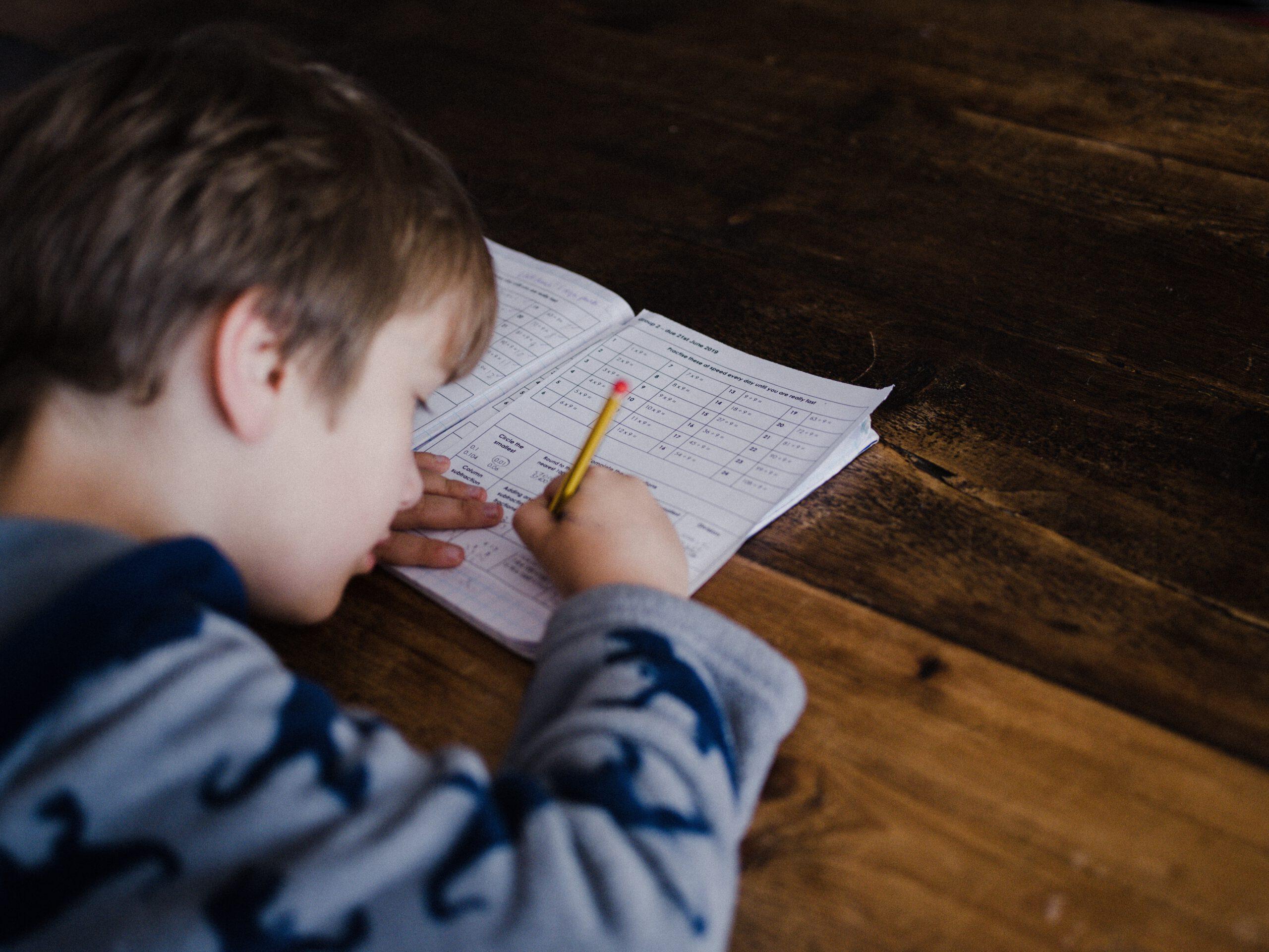 Poika kirjoittaa vihkoon